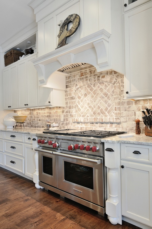 Luxury kitchen quartz countertops and brick backsplash by Construction Resources